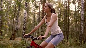 Beautiful young woman riding down the forest road on a sunny day. Beautiful young woman riding down the forest road on a sunny weekend day stock video