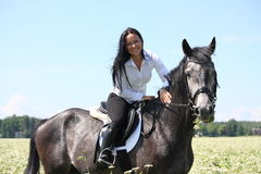 Beautiful young woman riding gray horse Stock Photography