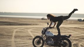 Beautiful young woman riding an old cafe racer  motorcycle and doing a trick. in the desert at sunset or sunrise. Female biker stock footage