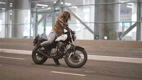 Beautiful young woman riding an old cafe racer motorcycle on street. Female biker at night city. Beautiful young woman riding an old cafe racer motorcycle on stock footage