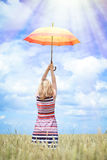 Beautiful young woman rising colorful umbrella on Royalty Free Stock Photography
