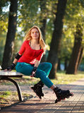 Beautiful young woman in roller skates sitting on park bench Royalty Free Stock Photo