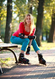 Beautiful young woman in roller skates sitting on park bench Royalty Free Stock Photos
