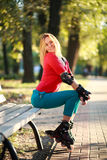 Beautiful young woman in roller skates sitting on park bench Royalty Free Stock Image