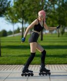 Beautiful young woman roller-skating Stock Image