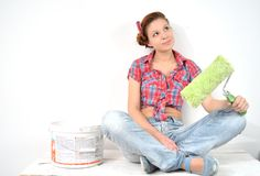Beautiful young woman with roller thinks over idea of repair Royalty Free Stock Images