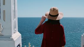 Excited brunette adventures in summer holidays. Beautiful young woman in romantic red dress and straw hat stands on top of pier or balcony overlooking blue stock video