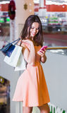 Beautiful young woman in a rose dress with shopping bags in the mall. Beautiful young woman in a rose dress with shopping bags and telephone and telephone in the Royalty Free Stock Photos