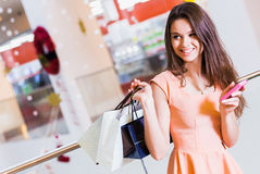Beautiful young woman in a rose dress with shopping bags  in the mall. Beautiful young woman in a rose dress with shopping bags and telephone and telephone in Royalty Free Stock Image