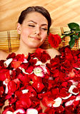Beautiful young woman in rose petal swim water. Royalty Free Stock Photography
