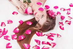Beautiful young woman on rose petals background. Photo with copy space royalty free stock photography