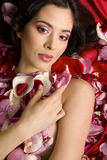 Beautiful young woman In rose's petals Stock Photography
