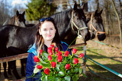 Beautiful young woman with roses and black horses Royalty Free Stock Image