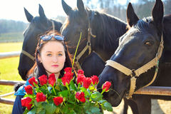 Beautiful young woman with roses and black horses Stock Photos