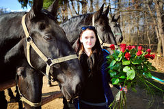 Beautiful young woman with roses and black horses Stock Photography