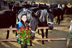 Beautiful young woman with roses and black horses Royalty Free Stock Photography