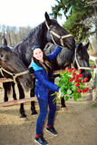 Beautiful young woman with roses and black horses Royalty Free Stock Images