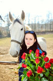 Beautiful young woman with roses and white horse Royalty Free Stock Photography