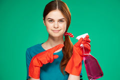 Beautiful young woman in rubber gloves on a green background holds a cleanser, cleaning, housework Royalty Free Stock Photography