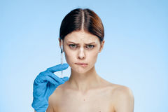 Beautiful young woman in rubber gloves holds a syringe, emotions, portrait, plastic surgery Royalty Free Stock Photography