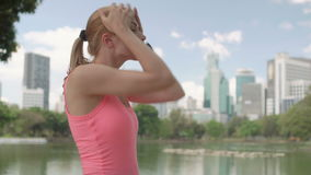 Beautiful young woman runner jogging in park. Fit female sport fitness training. Having a rest. Beautiful attractive young woman runner with a ponytail jogging stock video footage