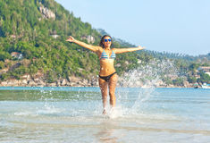 Beautiful young woman running along the beach and creates a spla Stock Images