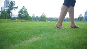 Beautiful young woman running barefoot on grass in the summer meadow.  stock footage