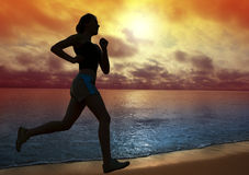 Beautiful young woman running on a beach. At sunset Royalty Free Stock Photos