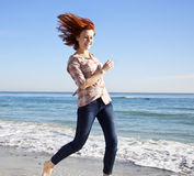 Beautiful young woman running on the beach Royalty Free Stock Images