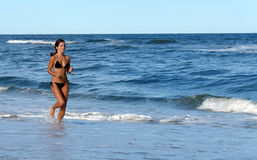 Beautiful young woman running on the beach Royalty Free Stock Photos