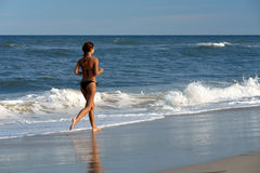 Beautiful young woman running on the beach. MD, USA Stock Photos
