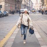 Beautiful young woman running in the city streets Stock Photography