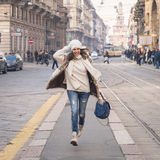 Beautiful young woman running in the city streets Royalty Free Stock Photo