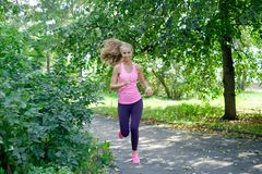 Beautiful young woman running in green park on sunny summer day.  Royalty Free Stock Image