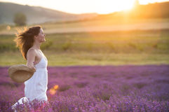 Beautiful young woman running through a lavender field. Beautiful young  healthy woman with a white dress running joyfully through a lavender field holding a Royalty Free Stock Photos