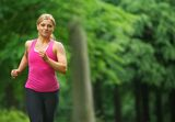 Beautiful young woman running in the park in sportswear stock photo