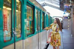 Beautiful young woman running to catch a train. On the platform of Parisian subway Royalty Free Stock Photo