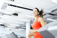 Beautiful young woman running on a treadmill in gym Royalty Free Stock Images