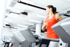 Beautiful young woman running on a treadmill in gym Royalty Free Stock Photo
