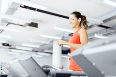 Beautiful young woman running on a treadmill in gym Royalty Free Stock Photos