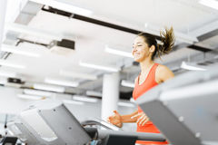 Beautiful young woman running on a treadmill in gym Royalty Free Stock Image
