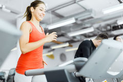 Beautiful young woman running on a treadmill in gym Stock Photos