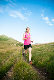 Beautiful young woman runns cross country on a mountian path at Stock Image