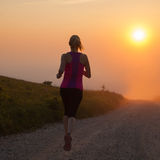 Beautiful young woman runs cross country on a mountain path Royalty Free Stock Images
