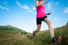 Beautiful young woman runs cross country on a mountain path at Stock Images