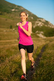 Beautiful young woman runs cross country on a mountian path at Royalty Free Stock Photography