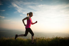 Beautiful young woman runs cross country on a mountian path at. Beautiful young woman runs on a mountian path at sunrise for morning exercizing and healthy life Stock Photography