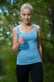 Beautiful young woman runs in forest - active runner running Royalty Free Stock Image