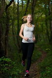 Beautiful young woman runs in forest - active runner running Stock Images