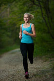 Beautiful young woman runs in forest - active runner running Royalty Free Stock Photos